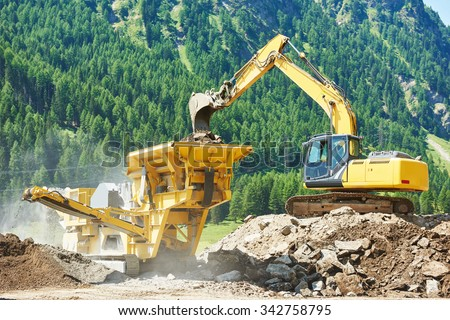 excavator loads the ground in the stone crusher machine during earthmoving works outdoors at mountains construction site - stock photo