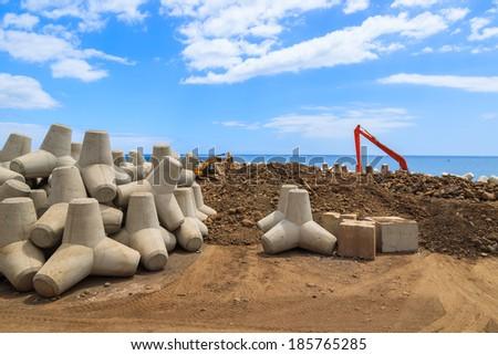 Excavator machine building new harbour on coast of Madeira island, Portugal - stock photo
