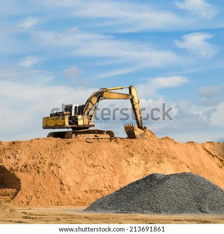 excavator machine loading dumper truck at sand quarry - stock photo