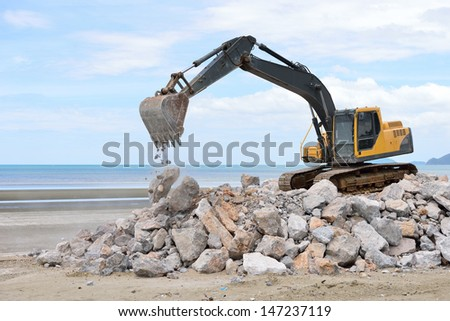 Excavator machine moves with raised bucket during moving stone - stock photo