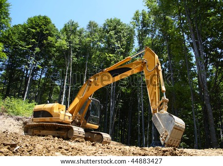 excavator makes a forest road - stock photo