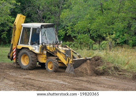 Excavator moving soil at a road construction - stock photo