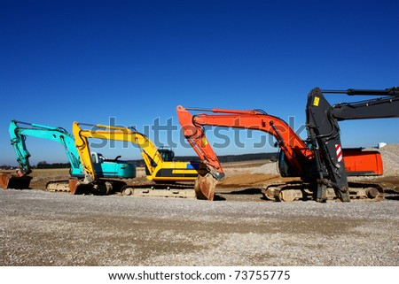 excavator on a building site on a sunny day - stock photo