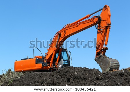 excavator on a compost heap against a blue sky - stock photo