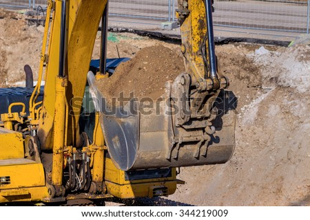 excavator on a construction site. excavator bucket with soil, earthworks. - stock photo