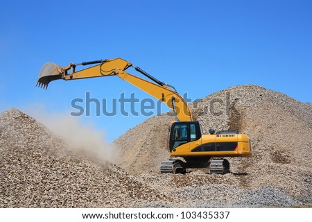 Excavator on a pile of rubble
