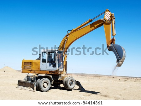 excavator on industrial field - stock photo