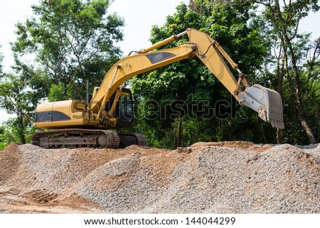 Excavator on mound and tree background - stock photo
