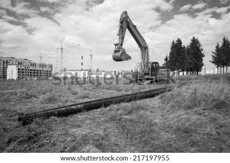 Excavator on the background buildings. - stock photo