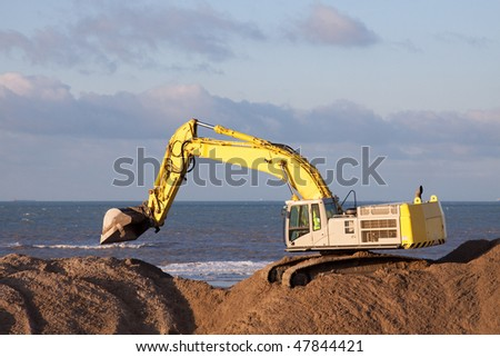 Excavator on the beach working with sand - stock photo