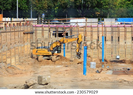 Excavator on the building site digging the ground  - stock photo