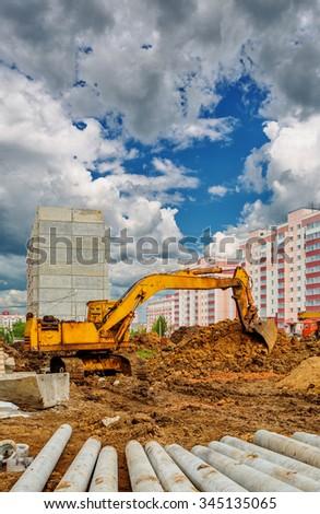 Excavator on the construction site beneath cloudy sky - stock photo