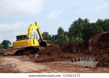 Excavator on working site, moving earth by its bucket - stock photo