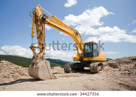 Excavator or digger (construction machinery) at a construction site outdoors - stock photo