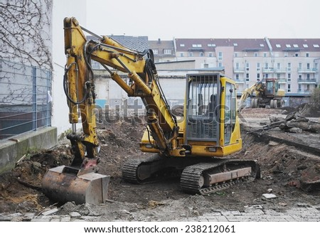 Excavator or digger on an urban building site being used for earthworks and clearing the site for construction - stock photo