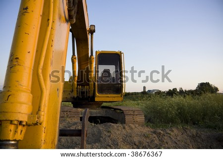 Excavator overlooking farmland with space for copy - stock photo