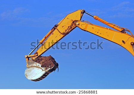 Excavator scoop full of dirt at a construction site. - stock photo