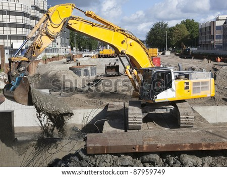 Excavator scooping mud on a urban construction site - stock photo
