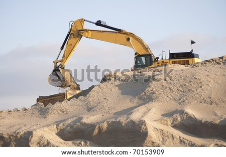 Excavator scooping sand on a truck - stock photo