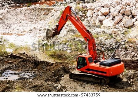 Excavator standing in sandpit with risen bucket - stock photo