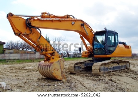 Excavator standing in the construction site - stock photo