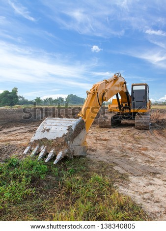 Excavator standing with cloudscape sky - stock photo