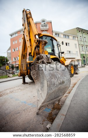 Excavator waitnig for work in a city - stock photo