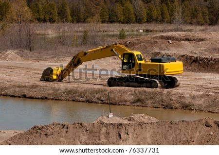 Excavator with a long arm in a sand quarry - stock photo