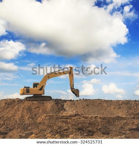 Excavator with blue sky - stock photo