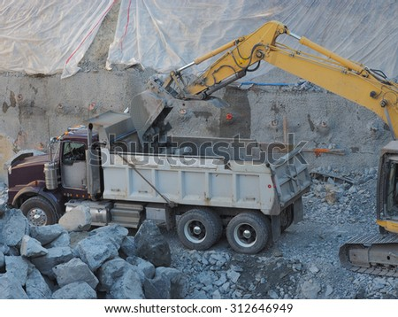 Excavator with large bucket loading broken rock into back of dump truck at construction site.  Photo shows truck, yellow boom of excavator, rock falling into box of truck blurred by motion