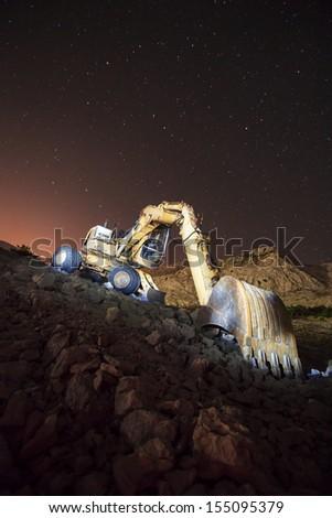 Excavator with night sky shot on long exposure - stock photo