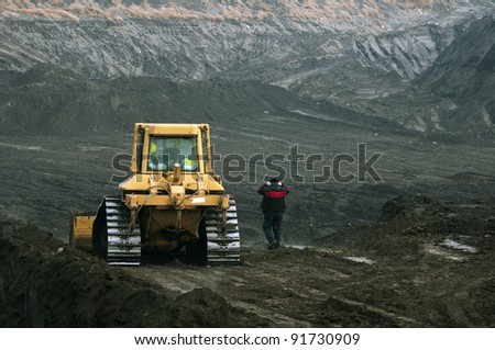 Excavator with tracks and worker - stock photo
