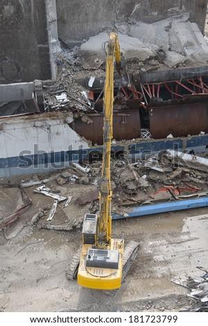 Excavator working in a demolition site - stock photo