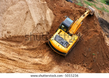 Excavator working on a heap of sand - stock photo