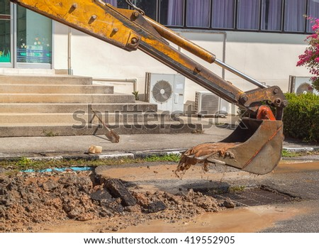 excavator working repair of pipe water and sewerage on road dig a hole to fix - stock photo