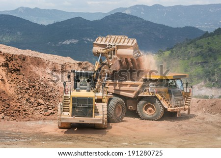 Excavator working with dump truck Mining trucks working side by side to uncover precious metals in an open mine  - stock photo