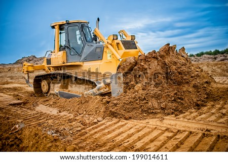 Excavator working with earth and sand in sandpit in highway construction site - stock photo