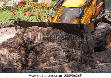 excavator works with the earth closeup - stock photo