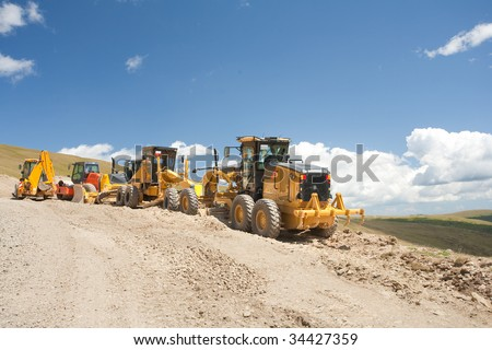 Excavators and construction machinery at a construction site outdoors - stock photo