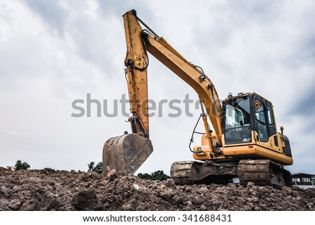 Excavators machine in construction site on sky background - stock photo