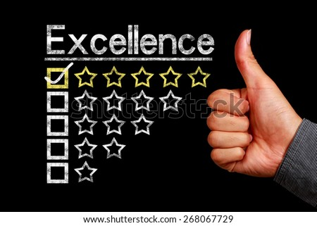 Excellence concept is on the blackboard with thumb up hand aside. - stock photo