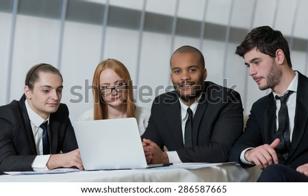 Excellent business agreement. Team of confident and motivated business partners are working on the project. All are wearing formal suits. Office business concept - stock photo