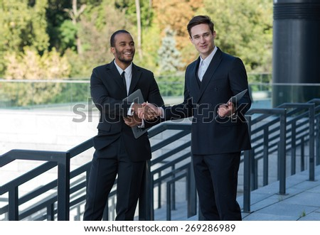 Excellent business agreement. Two confident and motivated businessmen are shaking hands. Both are wearing formal suits. Outdoor business concept