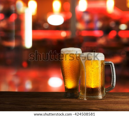 excellent light beer on a wooden table against the background of the city - stock photo