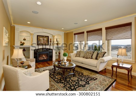 Excellent living room with decorative rug, white furniture and a fireplace. - stock photo