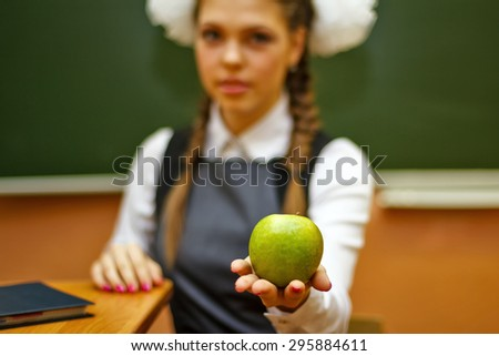 Excellent pupil holds a green apple on his hand. Focus on the apple. Back to school.