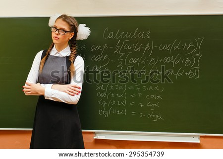 Excellent pupil stands at the blackboard with formulas for geometry. Lesson calculus. The concept of modern education. Back to school.