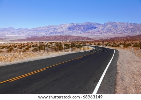 Excellent road, crossing Death Valley in the USA. The low dry bushes and mountains - stock photo