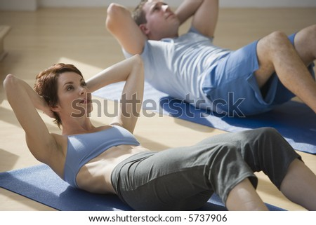 Excercising group doing situps on mats - stock photo