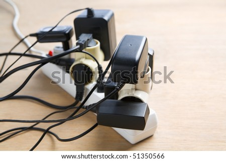 Excessive extension on power outlet, very dangerous. Small depth of field - stock photo